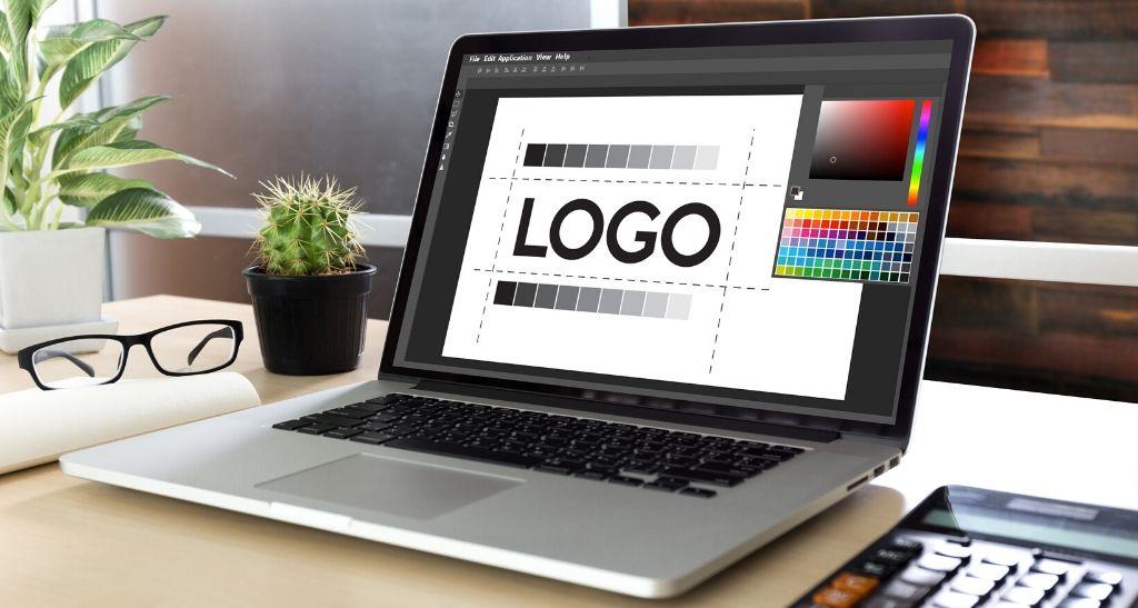 Un ordenador portátil con diseño de un logotipo en pantalla, sobre una mesa de escritorio con plantas y una calculadora
